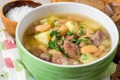 Σούπα βόειου κρέατος με τις πατάτες, τα φασόλια και τα πράσα στο κεραμικό κύπελλο στο υπόβαθρο πετρών Στοκ Εικόνες