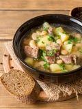 Σούπα βόειου κρέατος με τις πατάτες, τα φασόλια και τα πράσα στο κεραμικό κύπελλο στο υπόβαθρο πετρών Στοκ φωτογραφία με δικαίωμα ελεύθερης χρήσης