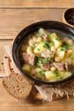 Σούπα βόειου κρέατος με τις πατάτες, τα φασόλια και τα πράσα στο κεραμικό κύπελλο στο υπόβαθρο πετρών Στοκ εικόνα με δικαίωμα ελεύθερης χρήσης