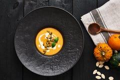 Σούπα κολοκύθας και καρότων με τους σπόρους και την κρέμα κολοκύθας στοκ εικόνα