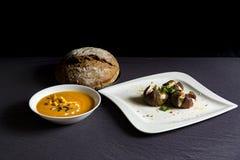 Σούπα κολοκύθας σε ένα κύπελλο με το ψωμί και τα ψημένα σύκα με το τυρί αιγών στοκ εικόνα
