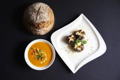 Σούπα κολοκύθας σε ένα κύπελλο με το ψωμί και τα ψημένα σύκα με το τυρί αιγών στοκ εικόνες