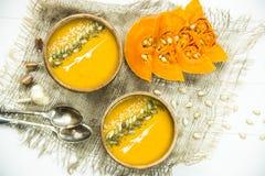 Σούπα κολοκύθας σε ένα πιάτο αργίλου που διακοσμείται με τους σπόρους κολοκύθας, τους σπόρους σουσαμιού, τα καρυκεύματα και την κ Στοκ φωτογραφία με δικαίωμα ελεύθερης χρήσης