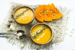 Σούπα κολοκύθας σε ένα πιάτο αργίλου που διακοσμείται με τους σπόρους κολοκύθας, τους σπόρους σουσαμιού, τα καρυκεύματα και την κ Στοκ Εικόνα