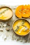Σούπα κολοκύθας σε ένα πιάτο αργίλου που διακοσμείται με τους σπόρους κολοκύθας, τους σπόρους σουσαμιού, τα καρυκεύματα και την κ Στοκ Εικόνες