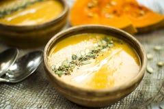 Σούπα κολοκύθας σε ένα πιάτο αργίλου που διακοσμείται με τους σπόρους κολοκύθας, τους σπόρους σουσαμιού, τα καρυκεύματα και την κ Στοκ εικόνα με δικαίωμα ελεύθερης χρήσης