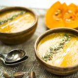 Σούπα κολοκύθας σε ένα πιάτο αργίλου που διακοσμείται με τους σπόρους κολοκύθας, τους σπόρους σουσαμιού, τα καρυκεύματα και την κ Στοκ Φωτογραφία