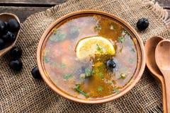 Σούπα κρέατος με τις μαύρες ελιές σε ένα ξύλινο υπόβαθρο με το ξύλινους κουτάλι και το σάκο Στοκ Εικόνα