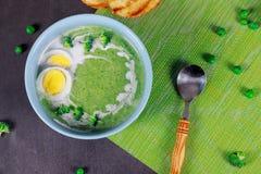 Σούπα κρέμας μπρόκολου και μαγειρευμένα αυγά κοτόπουλου σε έναν πίνακα Κλασικά ευρωπαϊκά τρόφιμα στοκ εικόνες