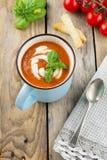Σούπα ντοματών σε ένα κεραμικό φλυτζάνι στο παλαιό ξύλινο υπόβαθρο Στοκ Εικόνες