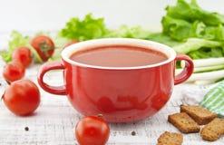 Σούπα ντοματών στο κόκκινο κεραμικό κύπελλο στο αγροτικό ξύλινο υπόβαθρο Hea Στοκ φωτογραφία με δικαίωμα ελεύθερης χρήσης