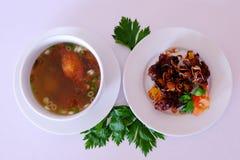 Σούπα πλευρών και ψημένα στη σχάρα πλευρά που παρουσιάζονται σε ένα πιάτο Στοκ Εικόνες