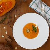 Σούπα, σπόροι, ψωμί και βασιλικός κολοκύθας στο πιάτο στο ξύλινο υπόβαθρο Στοκ Φωτογραφία