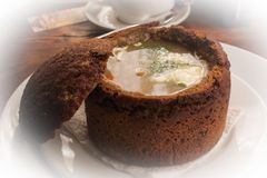 Σούπα στο κύπελλο ψωμιού στο άσπρο πιάτο στοκ φωτογραφίες