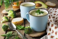 Σούπα του keramtcheskoy μπλε φλυτζανιού μπρόκολου και αβοκάντο στο παλαιό ξύλινο επιτραπέζιο υπόβαθρο Στοκ Εικόνα
