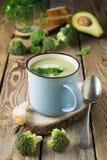Σούπα του keramtcheskoy μπλε φλυτζανιού μπρόκολου και αβοκάντο στο παλαιό ξύλινο επιτραπέζιο υπόβαθρο Στοκ Εικόνες