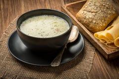 Σούπα τυριών σε ένα μαύρο πιάτο στο αγροτικό ξύλινο υπόβαθρο Στοκ εικόνα με δικαίωμα ελεύθερης χρήσης