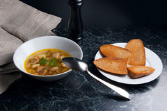 Σούπα φασολιών στο άσπρο πιάτο με το κουτάλι μετάλλων, διάφορη φρυγανιά στο μόριο Στοκ φωτογραφίες με δικαίωμα ελεύθερης χρήσης
