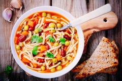 Σούπα Minestrone με τα λαχανικά και τα ζυμαρικά και ολόκληρες τις φρυγανιές σιταριού Στοκ Φωτογραφία