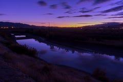 Σούρουπο κατά μήκος ενός ποταμού με την αντανάκλαση νερού του ουρανού Στοκ Φωτογραφία