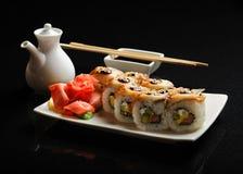 Σούσια και ρόλοι σε ένα τετραγωνικό πιάτο με το wasabi, τη σάλτσα σόγιας και chopsticks σε ένα μαύρο υπόβαθρο Στοκ Φωτογραφίες