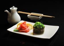 Σούσια και ρόλοι σε ένα τετραγωνικό πιάτο με το wasabi, τη σάλτσα σόγιας και chopsticks σε ένα μαύρο υπόβαθρο Στοκ Εικόνες