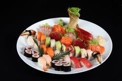 Σούσια και sashimi που αναμιγνύονται στο στρογγυλό άσπρο πιάτο Στοκ Εικόνες