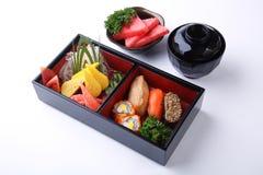 Σούσια που τίθενται σε ξύλινο Bento (ιαπωνικό καλαθάκι με φαγητό) που απομονώνεται στο λευκό Στοκ Εικόνα