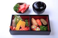 Σούσια που τίθενται σε ξύλινο Bento (ιαπωνικό καλαθάκι με φαγητό) που απομονώνεται στο λευκό Στοκ Εικόνες