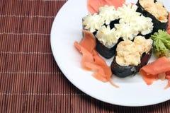 Σούσια στο άσπρο πιάτο πέρα από την ψάθινη κινηματογράφηση σε πρώτο πλάνο χαλιών αχύρου Στοκ Εικόνες