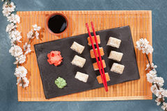 Σούσια στο πιάτο με chopsticks, την πιπερόριζα, τη σόγια, το wasabi και το sakura Στοκ φωτογραφία με δικαίωμα ελεύθερης χρήσης