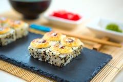 Σούσια της Maki με τα ψάρια θάλασσας και τυρί κρέμας στον πίνακα Ιαπωνική κουζίνα Σούσια ρόλων που τίθενται σε έναν μαύρο πίνακα  Στοκ Εικόνες