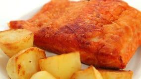 Σολομός που τηγανίζεται με τις πατάτες απόθεμα βίντεο