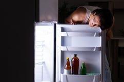 Σπάζοντας διατροφή ατόμων τη νύχτα κοντά στο ψυγείο στοκ φωτογραφία