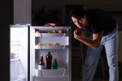 Σπάζοντας διατροφή ατόμων τη νύχτα κοντά στο ψυγείο στοκ εικόνες με δικαίωμα ελεύθερης χρήσης