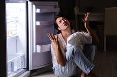 Σπάζοντας διατροφή ατόμων τη νύχτα κοντά στο ψυγείο στοκ φωτογραφία με δικαίωμα ελεύθερης χρήσης