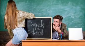 Σπάζοντας κανόνες Γυναίκα πειρασμός σπουδαστών Η μίνι φούστα σπουδαστών με τους προκλητικούς γλουτούς παραπλανεί το δάσκαλο Πειθα στοκ εικόνες με δικαίωμα ελεύθερης χρήσης