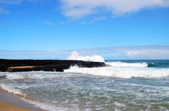 Σπάζοντας κύματα ενάντια στη μαύρη λάβα Kauai στοκ εικόνες