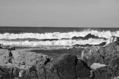 Σπάζοντας κύματα ενάντια στους βράχους σε γραπτό Στοκ Εικόνες