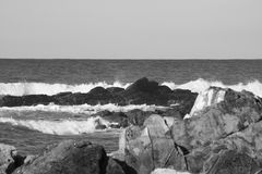 Σπάζοντας κύματα ενάντια στους βράχους σε γραπτό Στοκ φωτογραφίες με δικαίωμα ελεύθερης χρήσης
