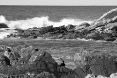 Σπάζοντας κύματα ενάντια στους βράχους σε γραπτό Στοκ φωτογραφία με δικαίωμα ελεύθερης χρήσης