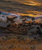Σπάζοντας κύματα στις δύσκολες αντανακλάσεις ακτών και ήλιων στο ηλιοβασίλεμα Στοκ εικόνες με δικαίωμα ελεύθερης χρήσης