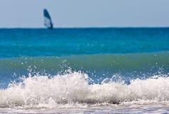 Σπάζοντας κύμα θάλασσας με ένα απομονωμένο windsurfer στο τοπίο υποβάθρου Στοκ φωτογραφίες με δικαίωμα ελεύθερης χρήσης
