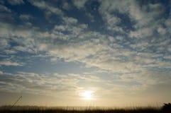 Σπάζοντας σύννεφα γουρνών ήλιων που χρωματίζουν τον ουρανό και την άγρια χλόη με Στοκ εικόνες με δικαίωμα ελεύθερης χρήσης