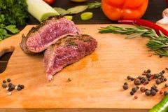 Σπάνιο βόειο κρέας ψητού στον τέμνοντα πίνακα με τα συστατικά Στοκ φωτογραφία με δικαίωμα ελεύθερης χρήσης