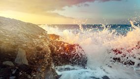Σπάσιμο κυμάτων στις πέτρες Ccoastal και στροφή στη θάλασσα αφρού στον ορίζοντα και το ηλιοβασίλεμα Στοκ εικόνες με δικαίωμα ελεύθερης χρήσης