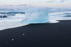 Σπάσιμο πάγου από τα παγόβουνα στη μαύρη παραλία άμμου Στοκ εικόνα με δικαίωμα ελεύθερης χρήσης
