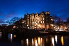 Σπίτια καναλιών του Άμστερνταμ που φωτίζονται στο σούρουπο Στοκ φωτογραφία με δικαίωμα ελεύθερης χρήσης