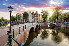 Σπίτια καναλιών του Άμστερνταμ στις αντανακλάσεις ηλιοβασιλέματος, Κάτω Χώρες Στοκ Φωτογραφίες