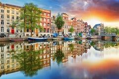 Σπίτια καναλιών του Άμστερνταμ στις αντανακλάσεις ηλιοβασιλέματος, Κάτω Χώρες, panor Στοκ Εικόνα